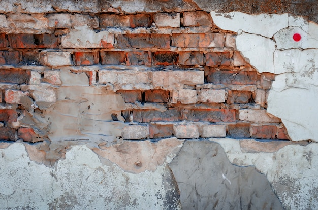 Het betonnen oppervlak met een grote steen en oude baksteen