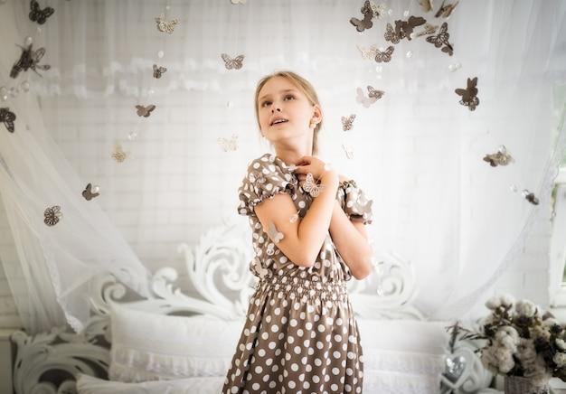 Het betoverde meisje in een blauwe jurk met stippen verheugt zich in magie met vlinders die ervan dromen in een fantastische sprookjeswereld te komen. het concept van fantasie en kinderachtig dagdromen