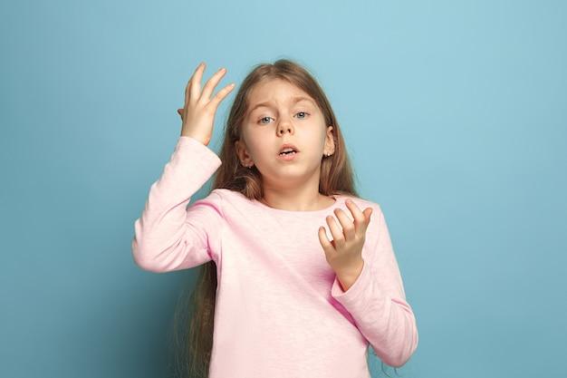 Het betreurenswaardige meisje. het trieste tienermeisje op een blauwe studioachtergrond. gezichtsuitdrukkingen en mensen emoties concept. trendy kleuren. vooraanzicht. halve lengte portret