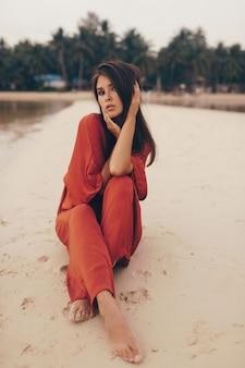 Het bevallige vrouw stellen op het strand, dat op zand in rode kleding zit