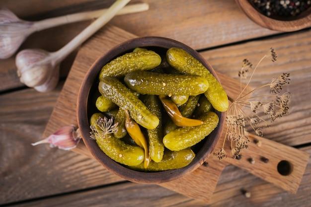 Het bewaren van ingelegde komkommers, kruiden en knoflook op een houten tafel. gezond gefermenteerd voedsel. home ingeblikte groenten.