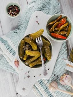 Het bewaren van ingelegde komkommers, paprika, kruiden en knoflook op een witte houten tafel. gezond gefermenteerd voedsel. home ingeblikte groenten.