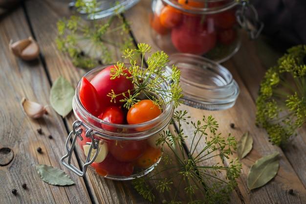 Het bewaren van verse en ingemaakte tomaten, kruiden en knoflook op houten lijst.