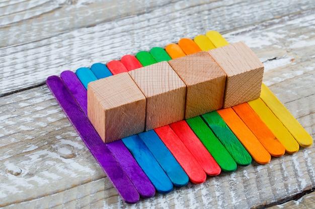 Het bewerken van concept met stokken, houten kubussen op houten achtergrond hoge hoekmening.