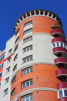 Het bewoonde hoge huis tegen de blauwe lucht