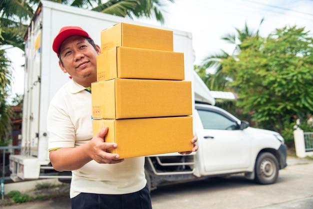 Het bezorgpersoneel staat glimlachend en houdt de pakjes voor de bestelwagen