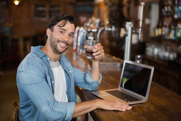 Het bier van de jonge mensenholding terwijl het zitten door laptop in bar