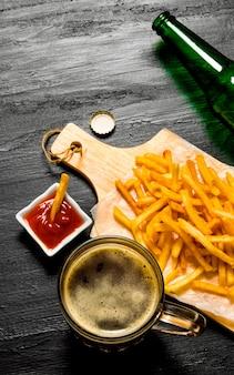 Het bierconcept bier en frietjes met tomatensaus op het bord