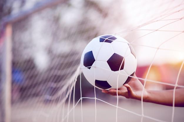 Het bijgesneden beeld van sporters die de bal en het voetbalveld vangen. sport-afbeelding concept.