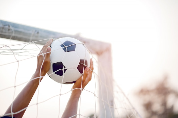 Het bijgesneden beeld van sporters die de bal en het voetbalveld vangen.