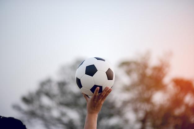 Het bijgesneden beeld van sportspelers die de bal en het voetbalveld vangen.
