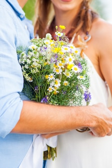 Het bijsnijdbeeld van romantisch paar met bloemen