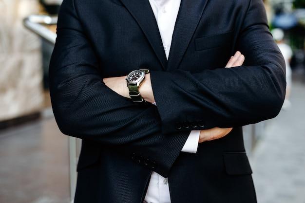 Het bijsnijden van beeld vouwde mannelijke handen, één hand met horlogeclose-up.