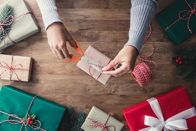 Het bindende koord van de vrouw rond de doos van de kerstmisgift na het verpakken met document