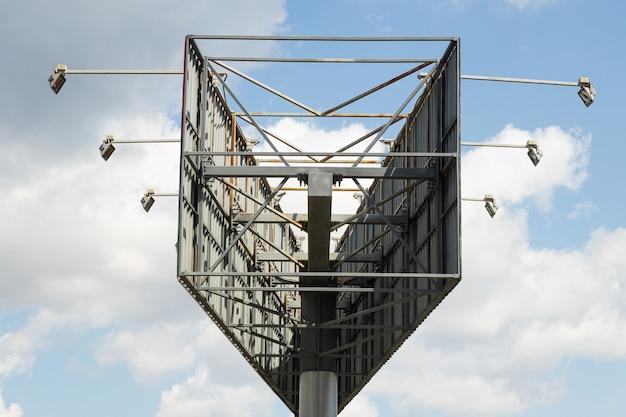 Het binnenaanzicht van de ruimte tussen twee grote billboards stalen constructie op hemel met wolken oppervlak.