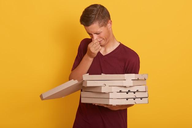 Het binnenschot van de jonge knappe leveringsmens met stank verwende pixxa, de mannelijke dozen van het holdingskarton, stellen geïsoleerd op geel, kerel die vrijetijdskleding dragen. levering concept.