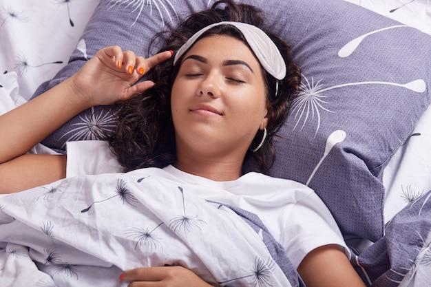 Het binnenschot van gelukkige vrouw die slaapmasker en witte t-shirt dragen terwijl het liggen in bed in ochtend, thuis slapen, ontspannend alvorens naar het werk te gaan, houdt ogen gesloten, hebbend donker haar. mensen concept.