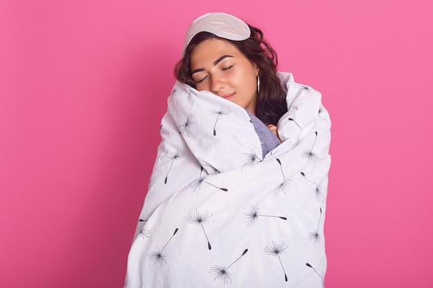 Het binnenschot van mooi donkerbruin kaukasisch meisje die witte deken en blinddoek op hoofd dragen, vrouw houdt ogen gesloten, stellend vroeg in ochtend, isolatedon roze studio. mensen concept.