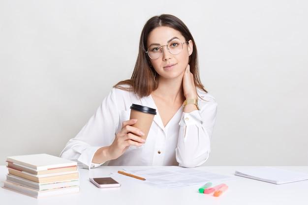 Het binnenschot van prettig ogende kaukasische vrouw houdt afhaalkoffie, gekleed in wit overhemd, direct camera bekijkt, heeft onderbreking na administratie. vrouwelijke leraar bereidt zich voor op lessen binnen