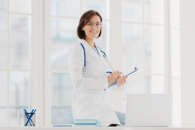 Het binnenschot van professionele vrouwelijke arts levert de hulp van de artsenzorg, stelt op desktop met laptop