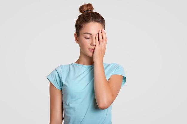 Het binnenschot van vermoeide sportvrouw behandelt gezicht met hand, gekleed in casual t-shirt, houdt ogen dicht, probeert geconcentreerd te zijn. vrouwelijke fitnesstrainer voelt zich uitgeput na aërobe trainingen, geïsoleerd