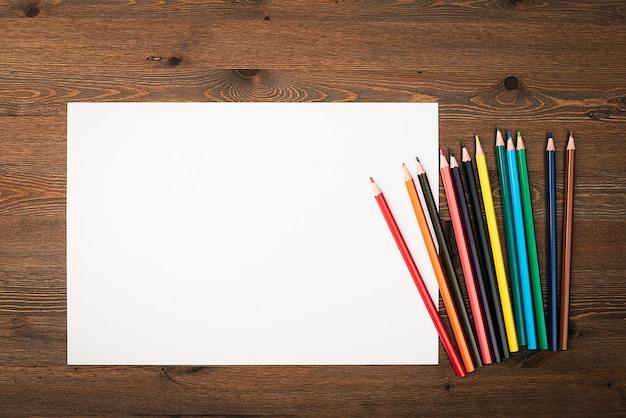 Het blad is puur wit en kleurpotloden om op een houten achtergrond te tekenen met een plek om te kopiëren. mock-up, mockup, lay-out.