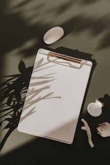 Het blanco stootkussen van het document bladklembord met exemplaarruimte, stenen, zeeschelpen, koraal in bloemenzonlichtschaduwen op donkergroen