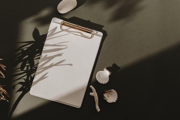 Het blanco stootkussen van het document bladklembord met stenen, zeeschelpen, koraal in bloemenzonlichtschaduwen op donkergroen