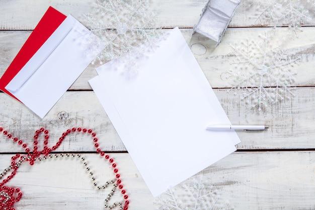 Het blanco vel papier op de houten tafel met een pen