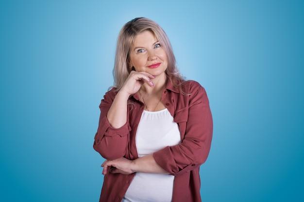 Het blanke vrouw stellen op een blauwe studiomuur die een wonder gebaart wat haar kin aanraakt en kijkt naar de camera