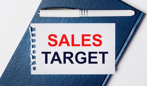 Het blauwe dagboek ligt op een lichte achtergrond. op heeft een witte pen en een stuk papier met de tekst sales target