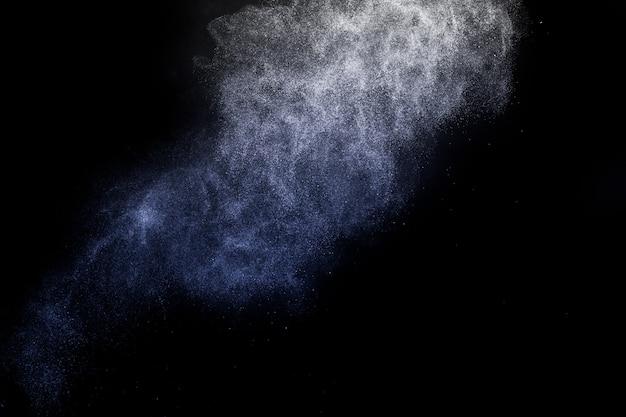 Het blauwe kosmetische poeder uitspreiden voor make-upkunstenaar en grafisch ontwerp op zwarte achtergrond