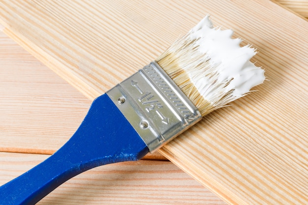Het blauwe penseel in witte verf ligt op een lichte houten plank. het begin van reparatiewerkzaamheden in huis. selectieve aandacht, kopieer ruimte
