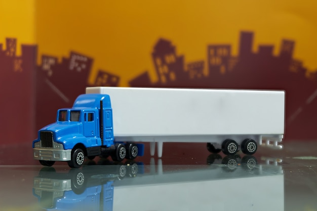 Het blauwe stuk speelgoed van de containervrachtwagen met spot op het zijaanzicht van de containerverwekker, selectieve nadruk, op onduidelijk beeldstad