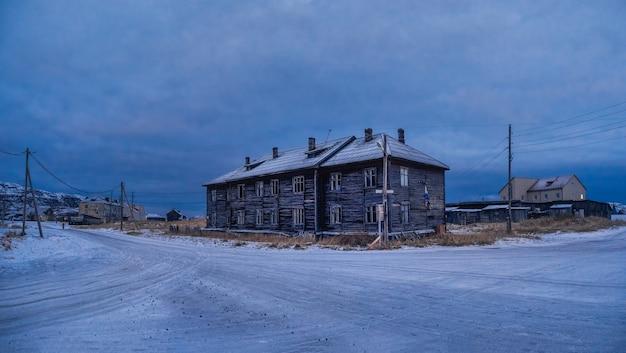 Het blauwe uur. vintage huizen op met sneeuw bedekte arctische heuvels. oud authentiek dorpje teriberka. kola-schiereiland. rusland.