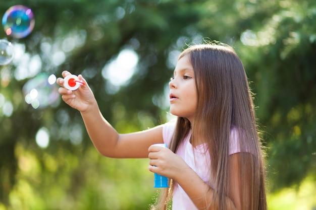 Het blazende zeepbels van het kinderenmeisje openlucht