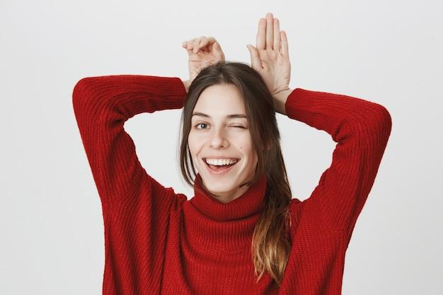 Het blije glimlachende meisje knipoogt en toont het gebaar van konijntjesoren