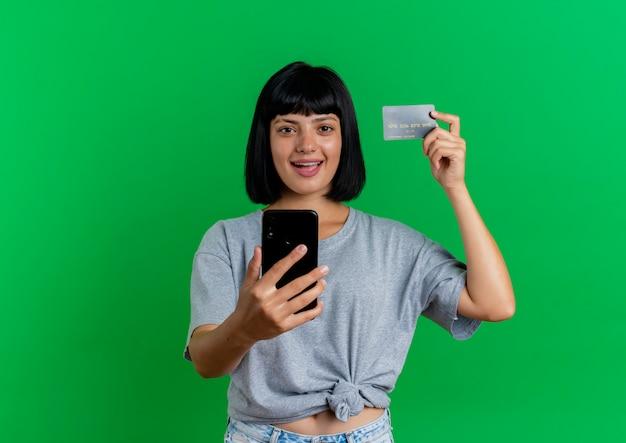 Het blije jonge donkerbruine kaukasische meisje houdt creditcard en telefoon