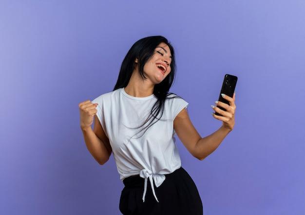 Het blije jonge kaukasische meisje houdt en bekijkt telefoon die vuist houdt
