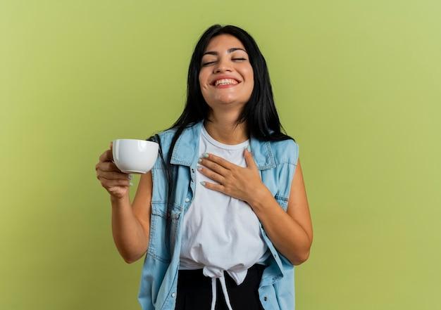 Het blije jonge kaukasische meisje houdt kop en legt hand op borst die op olijfgroene achtergrond met exemplaarruimte wordt geïsoleerd