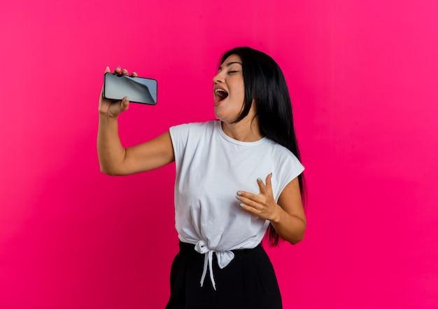 Het blije jonge kaukasische meisje houdt telefoon die beweert te zingen