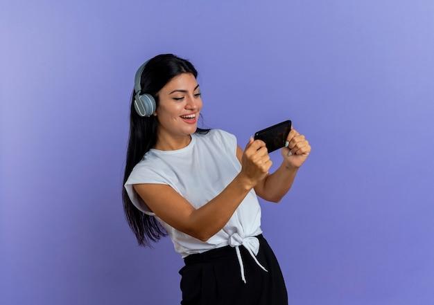 Het blije jonge kaukasische meisje op hoofdtelefoons houdt en bekijkt telefoon
