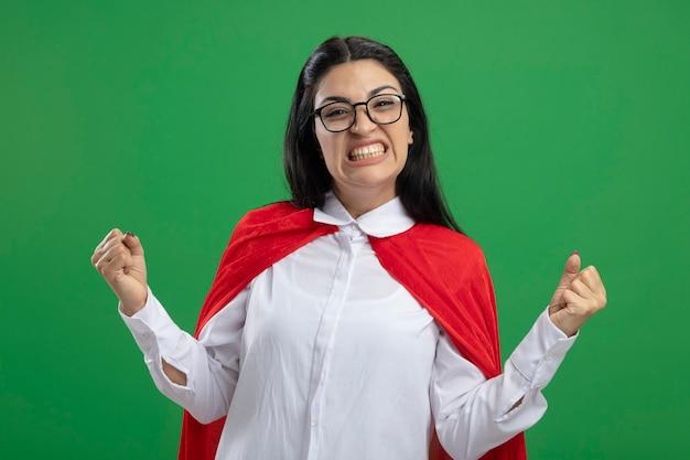 Het blije jonge kaukasische meisje van de winnaarsuperhero die glazen dragen die haar opgeheven vuisten balanceren en haar tanden tonen die op groene muur worden geïsoleerd