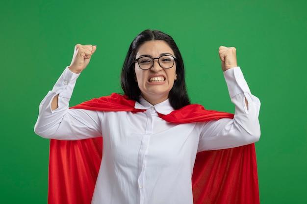 Het blije jonge kaukasische meisje van de winnaarsuperhero die glazen dragen die haar opgeheven vuisten glimlachend geïsoleerd op groene muur balanceren