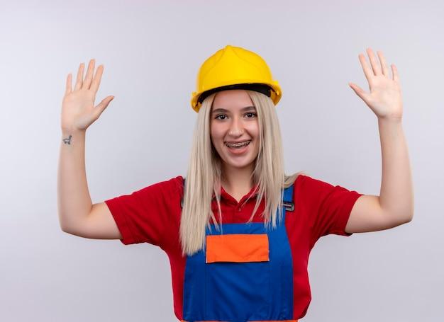 Het blije jonge meisje van de blonde ingenieursbouwer in eenvormig in tandsteunen die handen op geïsoleerde witte ruimte opheffen