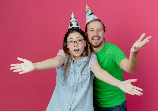 Het blije jonge paar dat partijhoed draagt kijkt het opheffen van handen die op roze muur worden geïsoleerd