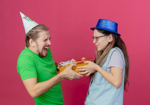 Het blije jonge paar houdt giftdoos staande aangezicht tot aangezicht geïsoleerd op roze muur