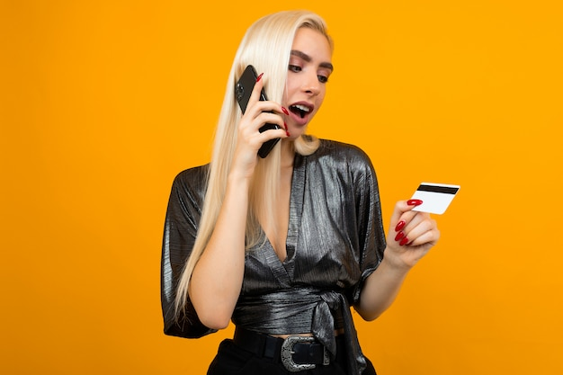 Het blije meisje doet telefonisch aankopen houdend een creditcard met een model op een gele studioachtergrond