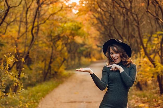 Het blije meisje in zwarte hoed stelt in het park