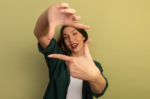 Het blije mooie blanke frame van vrouwengebaren met twee handen op olijfgroen
